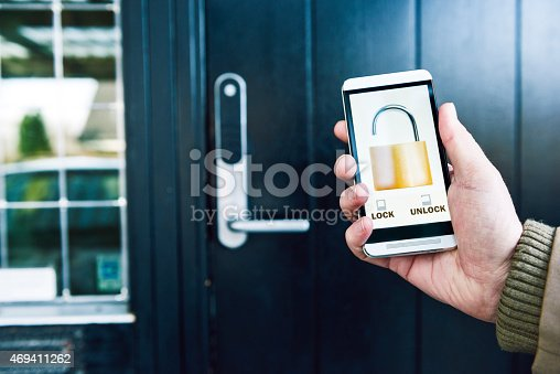 Photo of a hand holding a mobile phone. The phone shows a running app with the icon of an open lock. In the background is a front door to a house. Concept of home automation and internet of things, where products like locks connect to the internet and can be controlled remotely. Note: the image on the screen is my work.