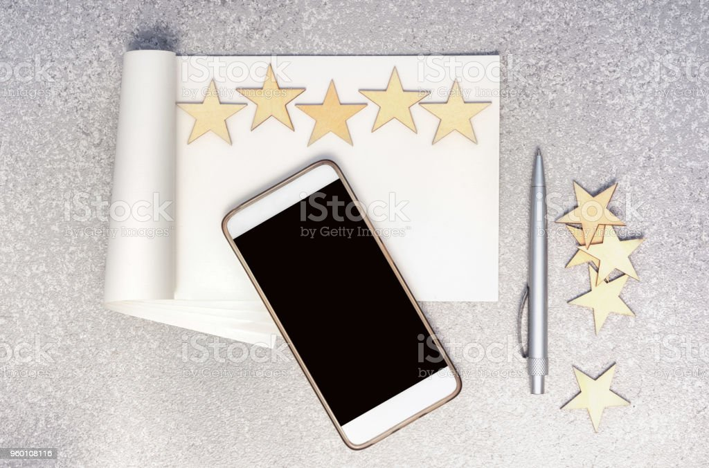 mobile phone, empty paper notebook, pen, five wooden stars in a row and group of stars at the side on a silver cement background, top view with copy space. Writing a 5 stars review concept. stock photo