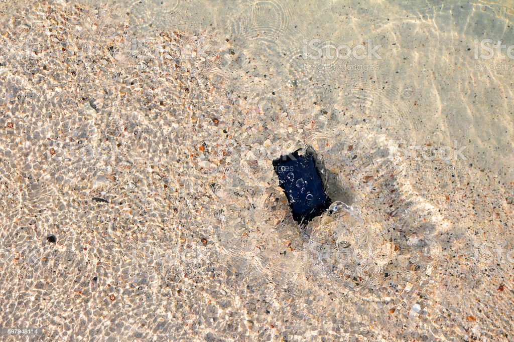 Mobile phone fall to the sea water. stock photo