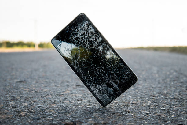 Mobile phone falling and crashes on asphalt, broken smartphone flying down to ground. Smashed, destroyed, damaged cellphone. Accident with gadget concept. Device need repairing. Crash test stock photo