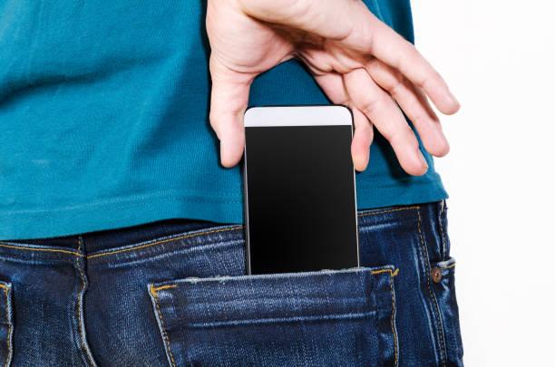 Mobile phone in a pocket - foto de acervo