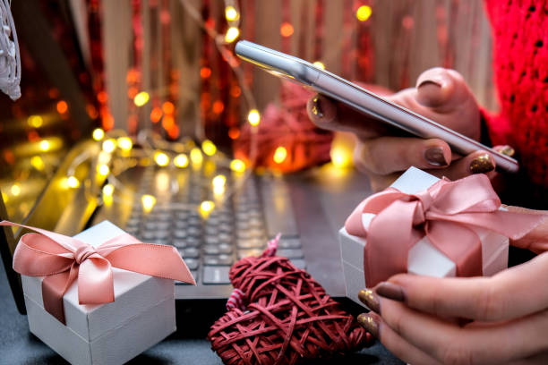Mobile phone in hand. Mobile applications. Online promotions and discounts. Holiday gifts and surprises. Present. Valentine's Day. Internet technologies. Shopping stock photo