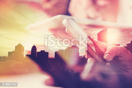 istock Mobile phone in hand with city skyline. 518957442