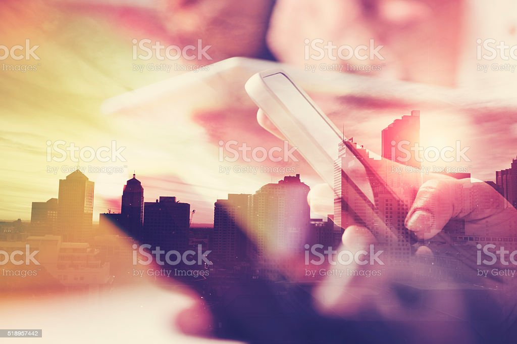 Mobile phone in hand with city skyline. stock photo