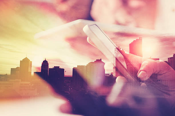 Telefone celular na mão com o horizonte da cidade. - foto de acervo