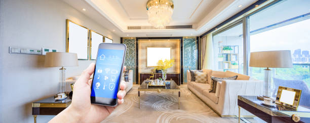 mobile phone in modern living room mobile phone with smart home app in modern living room home automation stock pictures, royalty-free photos & images