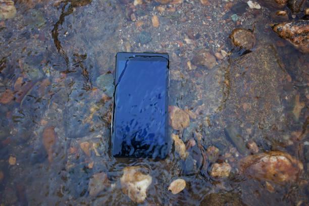 teléfono móvil en el río - foto de stock