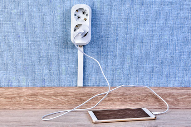 Mobile phone is charging with wall outlet. Smartphone is plugged into the charger which is inserted into a double outlet. battery charger stock pictures, royalty-free photos & images