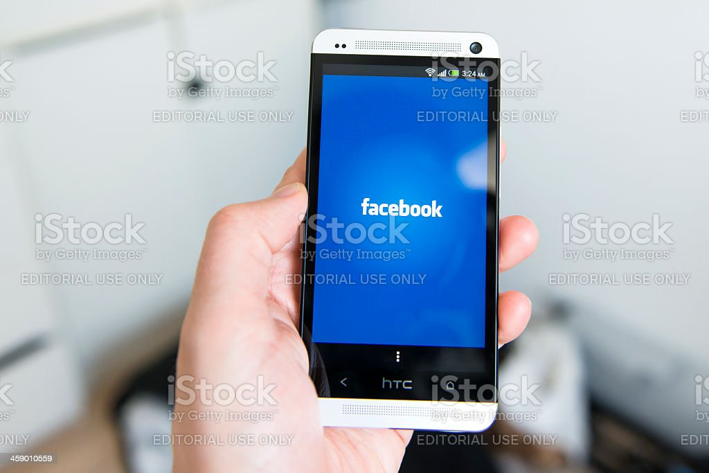 Mobile phone is launching an app for Facebook stock photo