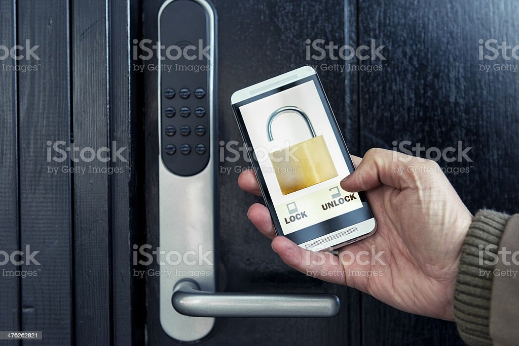 Mobile phone is used to lock and unlock front door stock photo