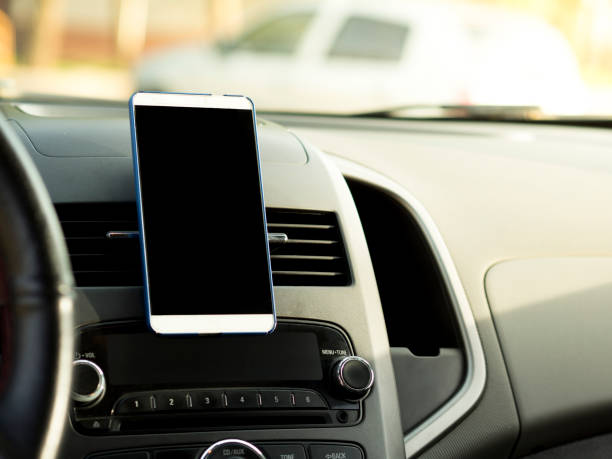 mobile phone located in the center of the vehicle console. Black screen phone in the car stock photo