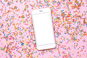 istock Mobile phone mock up and sweet multicolored sprinkles on pink pastel table in flat lay style. Fashion colour 1154162148