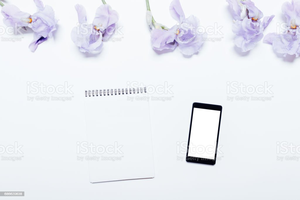 Mobile phone, notebook and blue flowers lie on a white background royalty-free stock photo