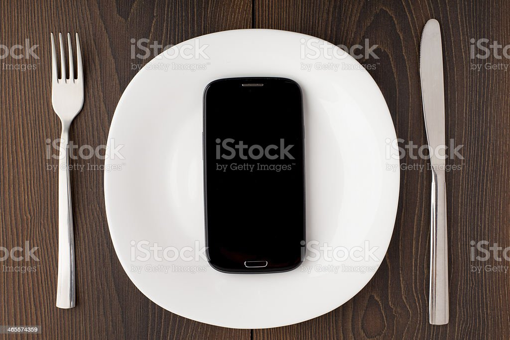 Mobile phone on a white plate royalty-free stock photo