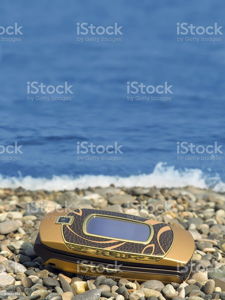 Mobile phone on beach royalty-free stock photo