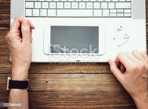 Female hand using smartphone while working at desk in office