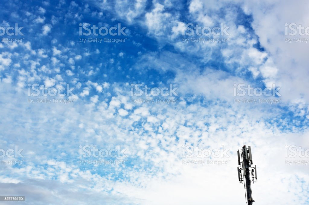 Mobile phone repeater tower against lightly clouded skly stock photo