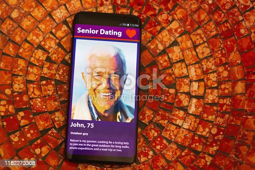 505935220istockphoto Mobile phone screen displays an old man on an internet dating site 1182273308