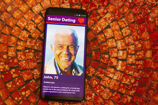 505935220 istock photo Mobile phone screen displays an old man on an internet dating site 1182273308