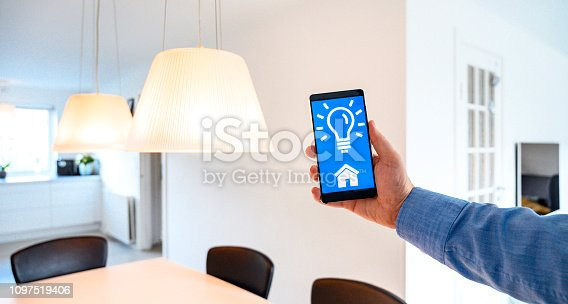 istock Mobile phone shows app to control light in smart home 1097519406
