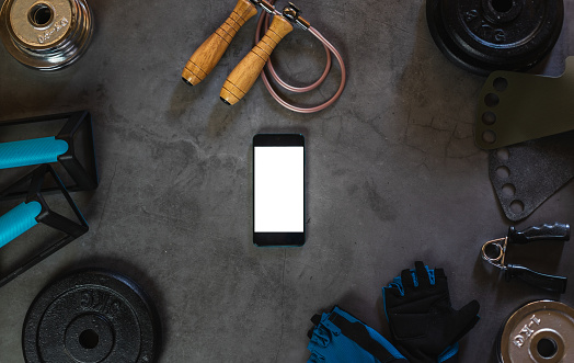 Mobile phone surrounded by different elements for sports training such as dumbbells, plates for weights, grip for push-ups, a rope to jump ...
