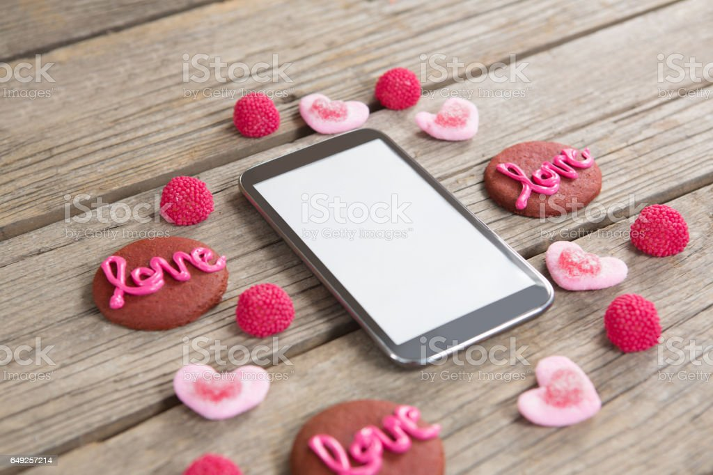 Mobile phone surrounded with cookies and confectionery stock photo