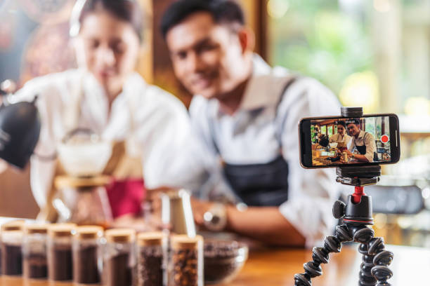 Mobile phone taking Video to two Asian Barista presenting a cup of coffee, dripping coffee show to audience in coffee shop,making espresso and americano, Small business owner and startup concept