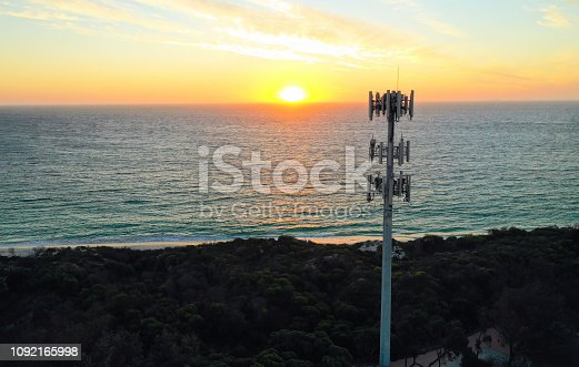 Aerial view of a cell phone tower (mobile phone tower) at sunset, with the orange sun setting above a blue ocean and clouds in the sky