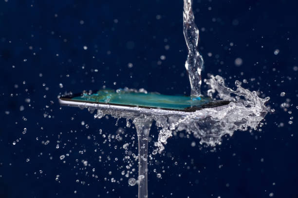 Mobile phone water resistant. Test waterproof mobile phone Splash and drops of water over a mobile phone. Testing water resistance of  waterproof mobile phone slow motion stock pictures, royalty-free photos & images