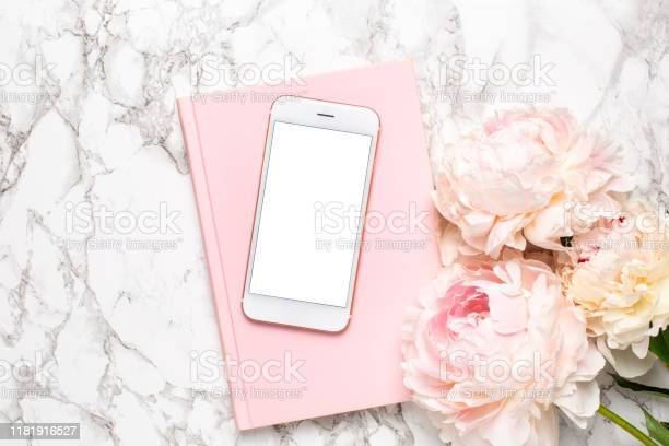 Mobile phone with a white and pink notebook and piony flowers on a picture id1181916527?b=1&k=6&m=1181916527&s=612x612&h=ucxnphtpsfh5nkb8ifb0hzaoogyfm kxooq7lupaw u=