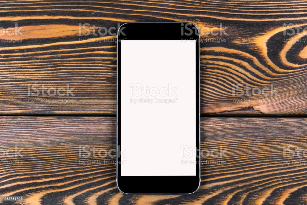 Mobile phone with blank screen mock up isolated on wood table background. Smartphone on wood table. Smartfone white royalty-free stock photo
