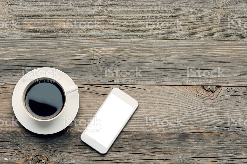 Mobile phone with coffee on a wooden table.