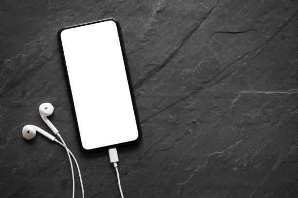 téléphone mobile avec écran vide et écouteurs sur la surface de la pierre noire - écouteurs intra auriculaires photos et images de collection