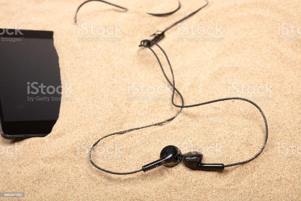해변에서 모래에 헤드폰으로 휴대 전화 - 로열티 프리 0명 스톡 사진