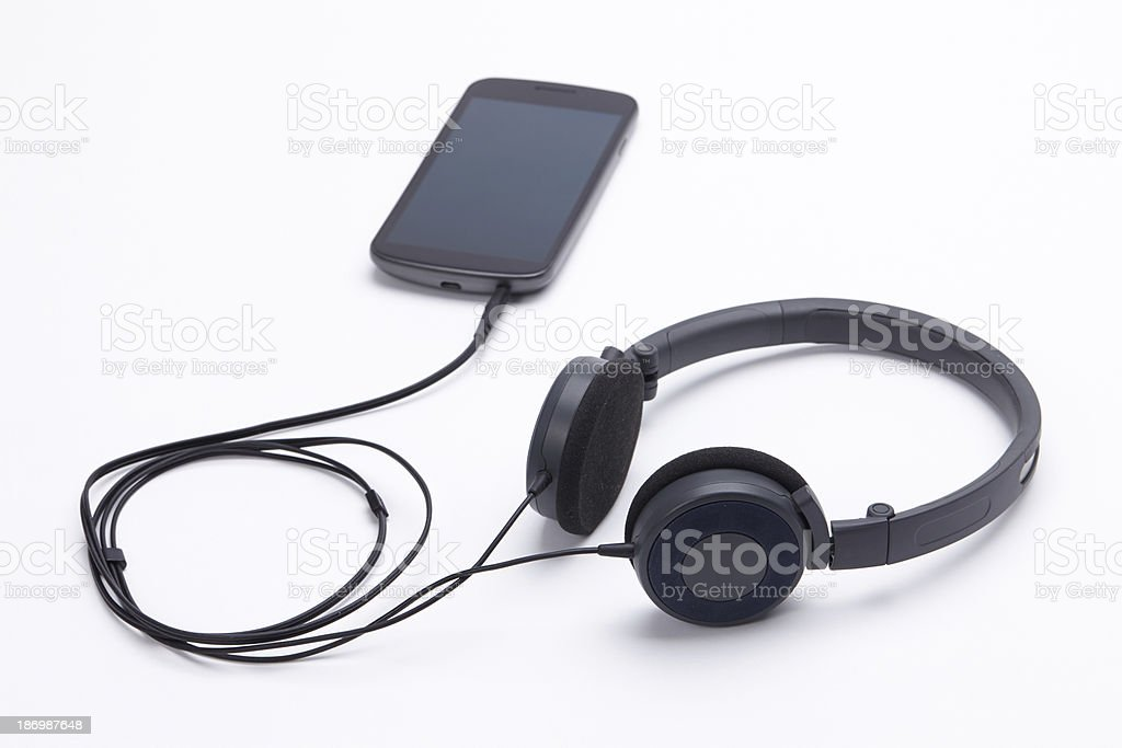 Mobile phone with headphones on white background royalty-free stock photo