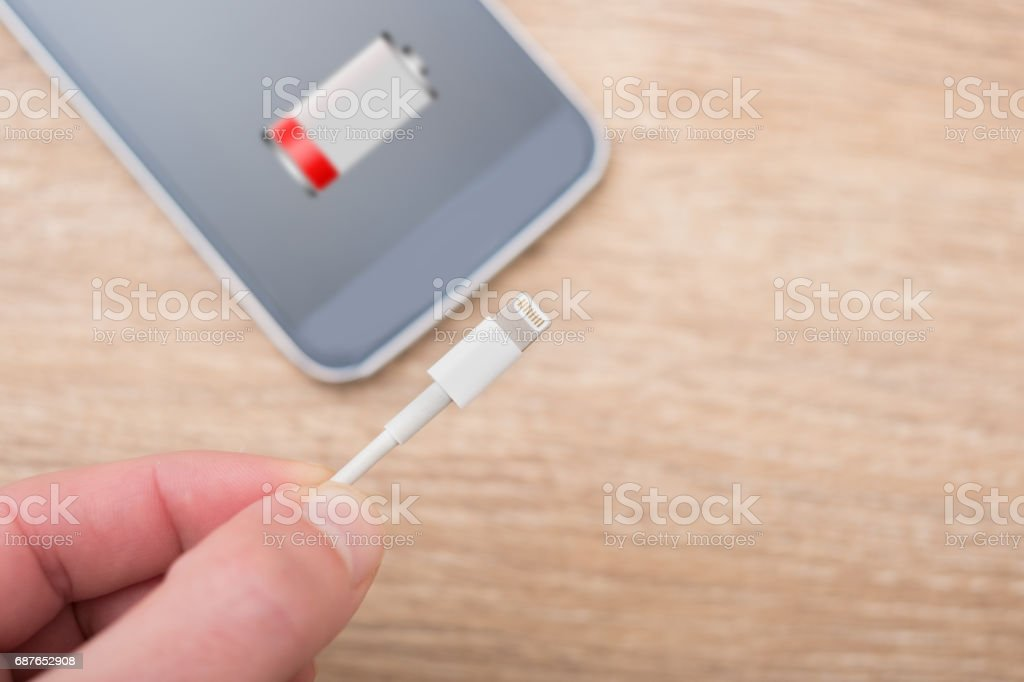 Mobile phone with low battery symbol on the screen - foto stock