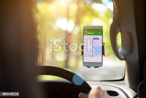 istock mobile phone with map GPS navigation in car. toned at sunset. 985408228