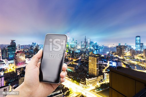 istock mobile phone with modern city at night 803599672