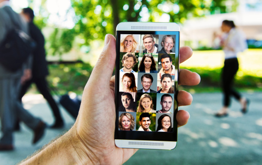 Concept of social networking with the mobile phone. Hand holds a smart phone with profile photos of 15 different people. From teenagers to seniors.