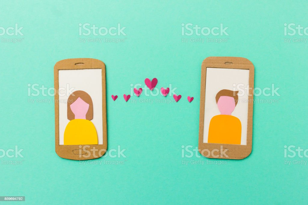 Mobile phone with red hearts flying from the screen - paper illustration image concept for online dating, dating apps stock photo