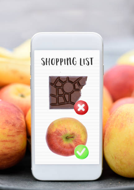 Mobile phone with shopping list healthy vs unhealthy no chocolate eat an apple dieting stock photo