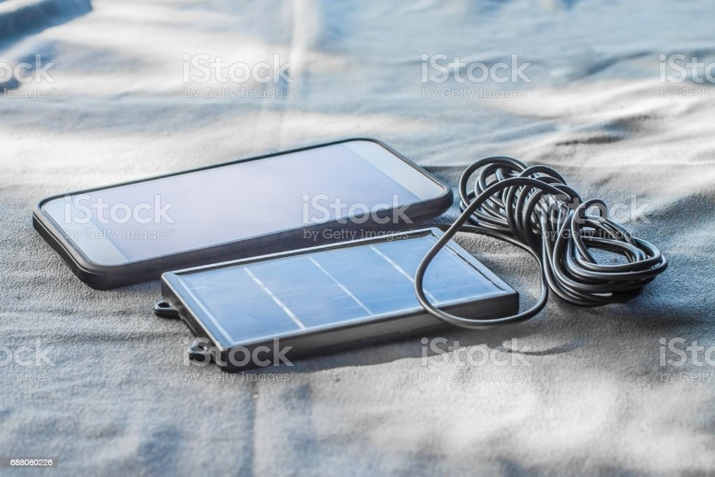 Mobile phone with solar energy charger stock photo