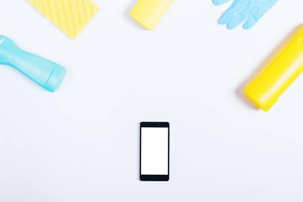 handy, gelbe und blaue flasche waschmittel und ein schwamm auf einem weißen tisch - bindewörter stock-fotos und bilder