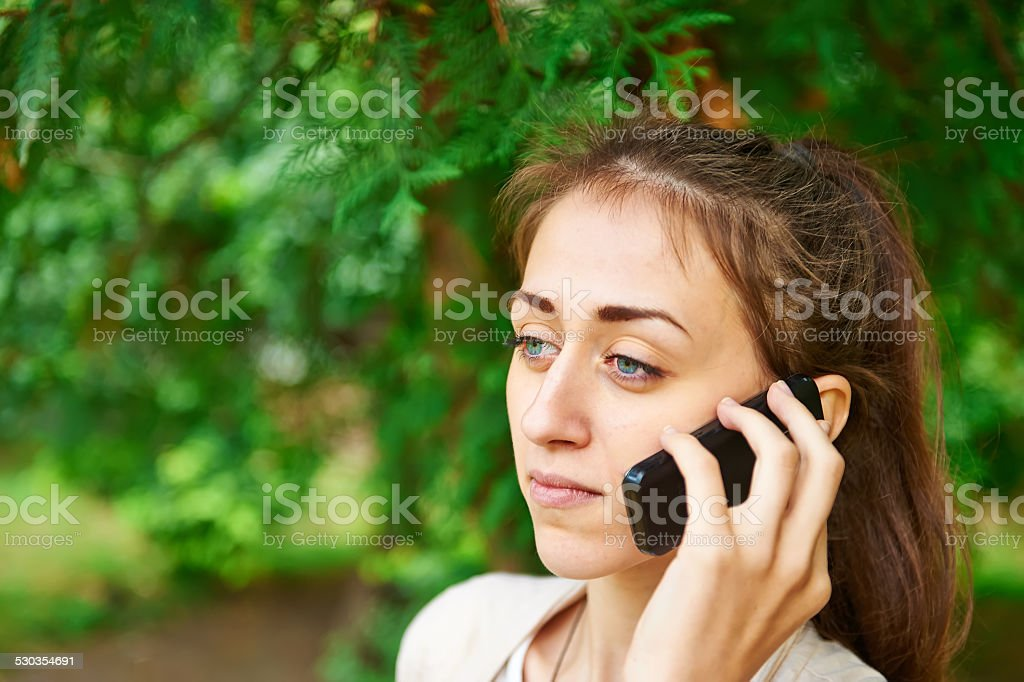 Mobile phone, young woman, conversation, summer, green trees background. stock photo
