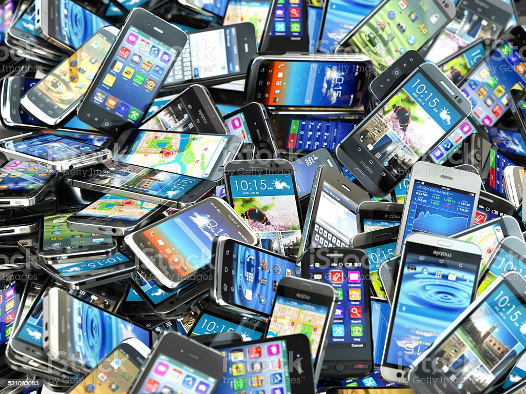 Mobile phones background. Pile of different modern smartphones. stock photo