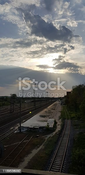 Mobile photography. Vertical image of the railway junction. Sun rays penetrate through the dramatic cloudy sky. In the background, the railway infrastructure: lighting, auxiliary towers, supporting supports.