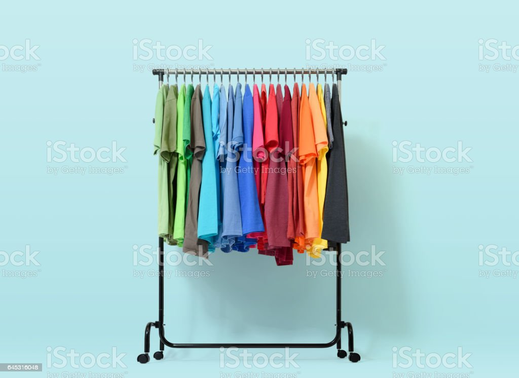 Mobile rack with color clothes on light blue background stock photo