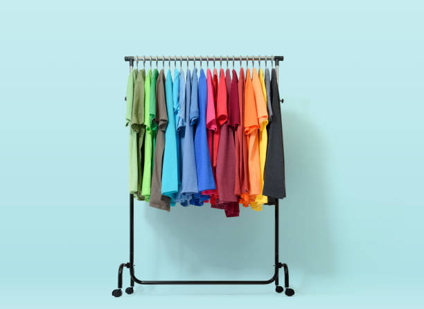 mobile rack with color clothes on light blue background - część garderoby zdjęcia i obrazy z banku zdjęć
