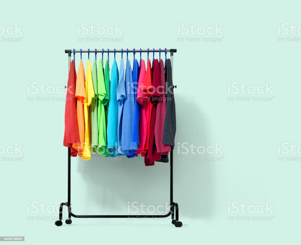 Mobile rack with color clothes on light green background stock photo