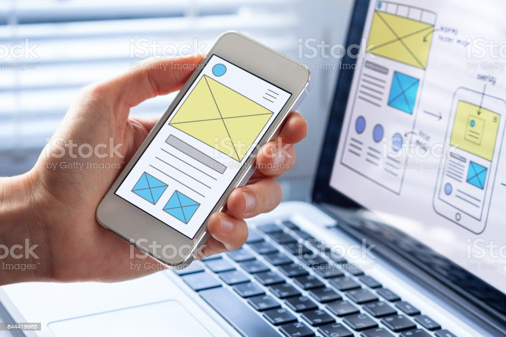 Mobile responsive website development, wireframe design preview on smartphone screen stock photo